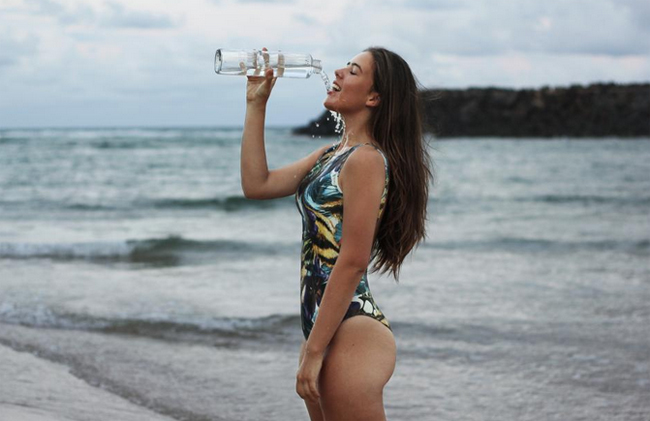 Girl in beach drinking water from bottle